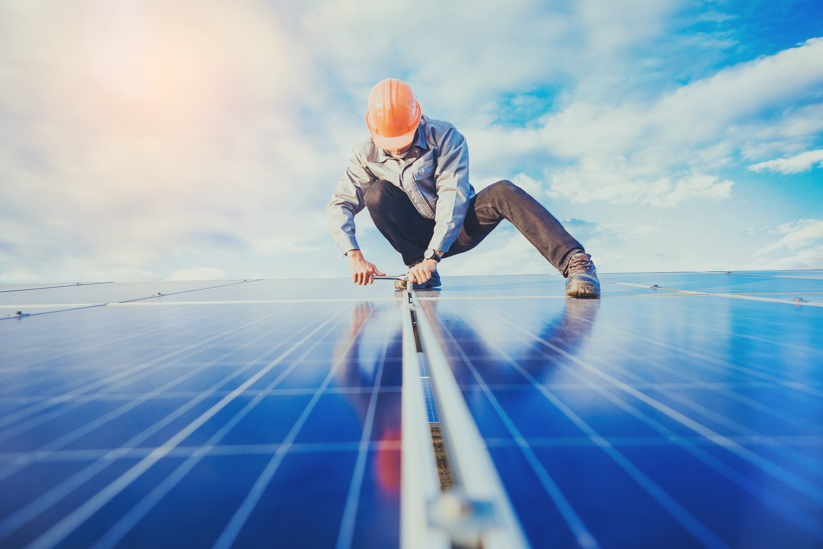 Electrical and instrument technician use wrench to maintenance electric system at solar panel field